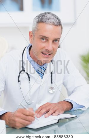 Doctor writing on diary at his desk in medical office