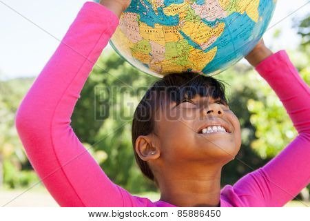 Cute little girl holding globe on a sunny day