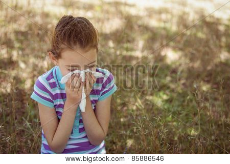 Cute little girl blowing her nose in park on a sunny day
