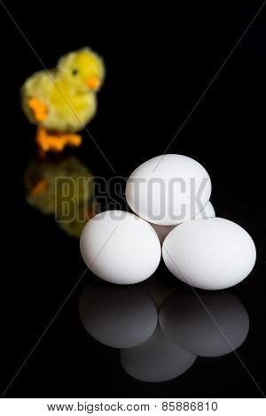 Eggs On A Black Background And A Mechanical Chicken