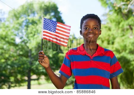 Little boy waving american flag on a sunny day