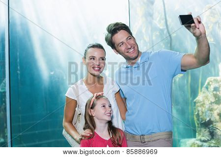 Happy family taking a selfie at the aquarium
