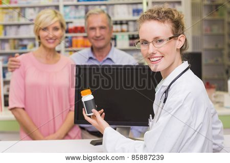 Pharmacist showing medicine jar to a customer at pharmacy