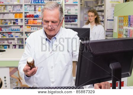 Pharmacist looking at medicine bottle at pharmacy