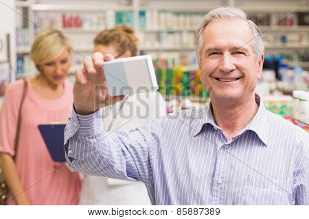 Costumer holding up medicine box at pharmacy