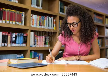 Student sitting in library writing at the university