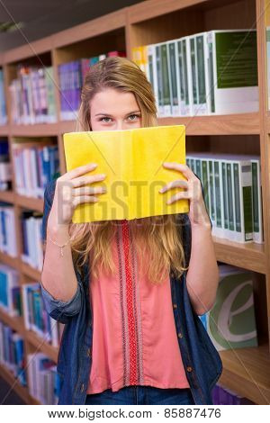 Student covering face with book in library at the university