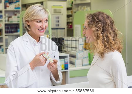 Pharmacist showing blister packs to costumer at pharmacy