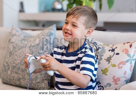 Little boy playing video games on the couch at home in the living room