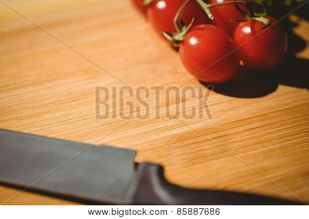 Cherry tomatoes and knife on chopping board with copy space