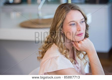 Thoughtful blonde woman at home