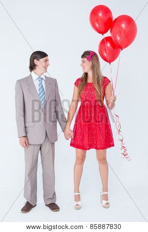 Smiling geeky couple standing hand in hand on white background