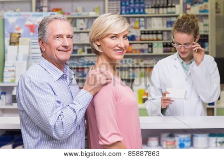 Costumers smiling to camera at pharmacy