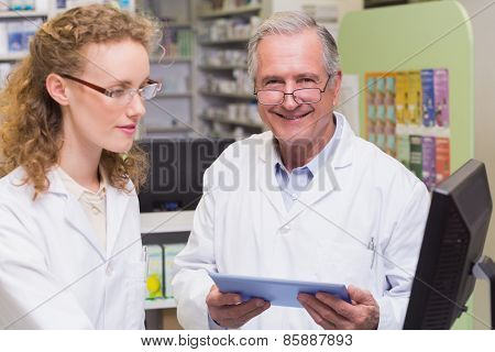 Team of pharmacists using laptop pc and computer at pharmacy