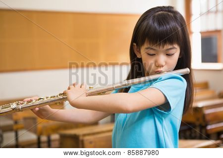 Cute pupil playing flute in classroom at the elementary school