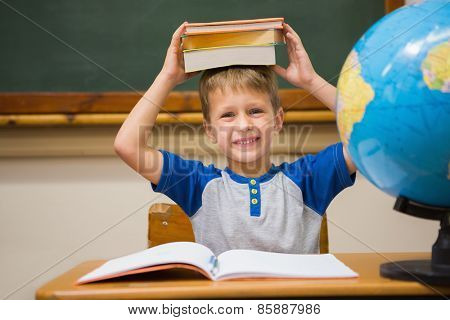 Pupil holding books on his head at elementary school