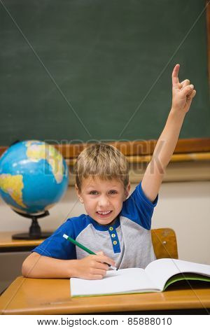 Pupils raising hand in classroom at the elementary school