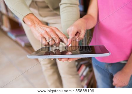 Teacher and pupil touching tablet screen at elementary school