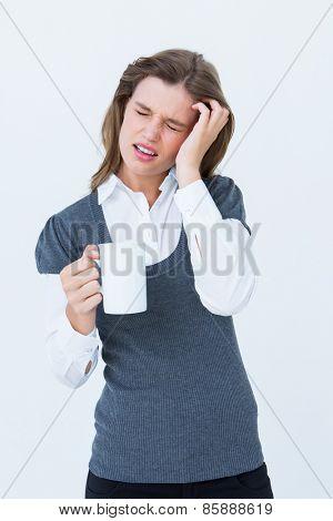 Woman with headache holding mug on white background
