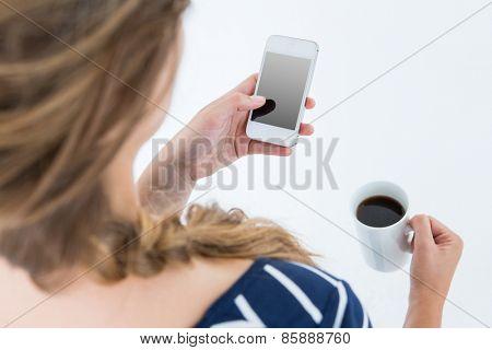 Woman using smartphone and holding mug on white background