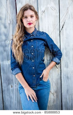 Pretty woman looking at camera with hands in pockets on wood surface