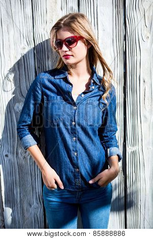 Pretty woman with hands in pocket on wooden surface