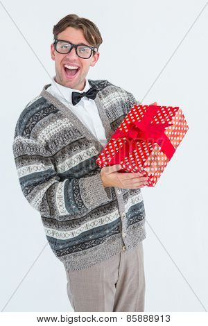 Happy geeky hipster with wool jacket holding present on white jacket