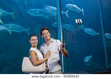 Happy couple using selfie stick at the aquarium