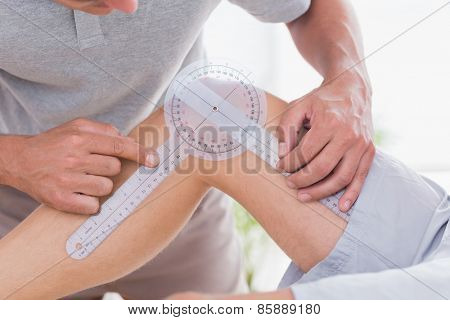 Doctor examining man leg in medical office