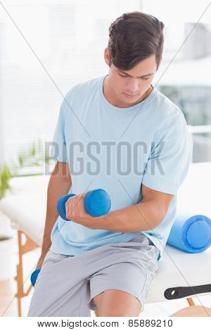 Young man training with dumbbells in medical office