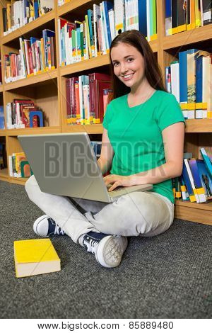 Student sitting on floor in library using laptop at the university