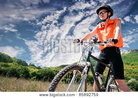Mountain female Biker and blue sky background