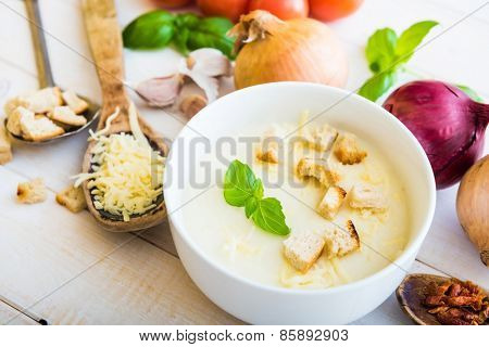 onion soup puree in a white plate with vegetables on the table