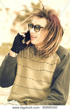 Young Rasta Guy Outdoor Talking With Smartphone With A Warm Filter Applied