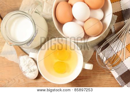 Eggs and whisk on wooden table