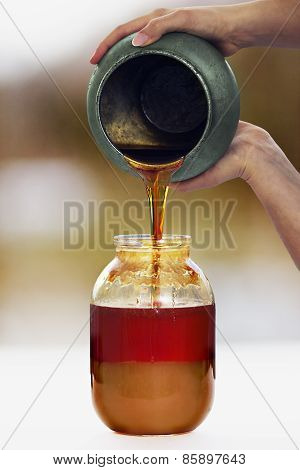 Woman's Hands Pours A Honey From A Pot To A Jar