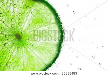 Lime with bubbles of soda isolated on white background