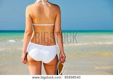 Young woman in white bikini standing on the beach