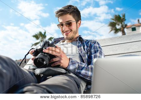 Young photographer with laptop and photo camera