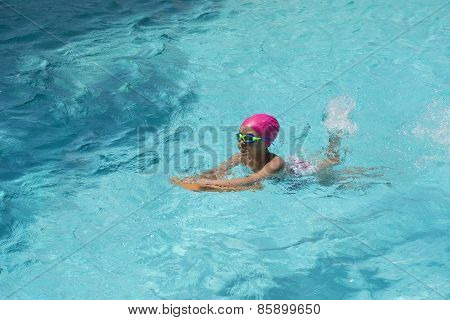 Little Young Girl Swimming In Blue Water