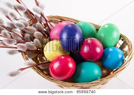 Wicker Basket With Colored Eggs And Willow Branches On A White Background