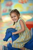 image of carousel horse  - Little girl with fairground horse in park outdoor - JPG