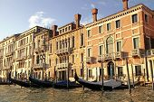 stock photo of gondola  - Beautiful view with typical venetian houses and gondola on the Grand Canal, Venice, Italy. Gondola is one of the symbols of Venice and major mode of touristic transport in Venice.