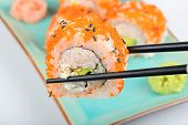 stock photo of masago  - Sushi roll with black chopsticks and other maki on the background - JPG