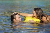 stock photo of bathing  - Happy couple playing on the beach in summer vacation while bathing - JPG