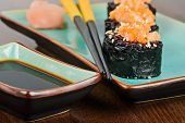 stock photo of chopsticks  - Baked sushi rolls with black rice and salmon served on turquoise plate with pickled ginger soy sauce and black chopsticks. Very shallow depth of field. Focus on the chopsticks.