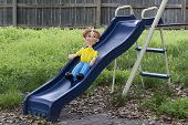 stock photo of swingset  - Twisted balloon art made into a person sliding down a blue slide in back yard with overgrown green grass - JPG