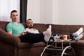 Постер, плакат: Smiling Male Friends Playing Video Games At Home