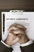 picture of mandate  - Man with clasped hands with divorce agreement on desk - JPG