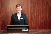 picture of receptionist  - Beautiful stylish hotel receptionist standing behind the service desk in a hotel lobby looking at a guest with a friendly smile - JPG